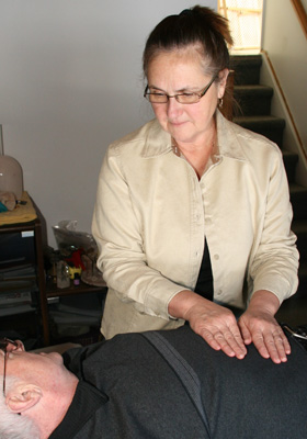 Photo of helen Sladden working with a reiki client
